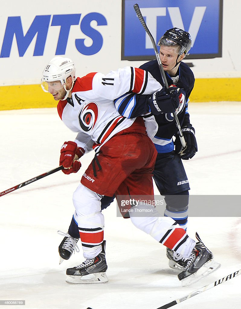 <a gi-track='captionPersonalityLinkClicked' href=/galleries/search?phrase=Jordan+Staal&family=editorial&specificpeople=533044 ng-click='$event.stopPropagation()'>Jordan Staal</a> #11 of the Carolina Hurricanes gets tangled up with <a gi-track='captionPersonalityLinkClicked' href=/galleries/search?phrase=Jacob+Trouba&family=editorial&specificpeople=8050718 ng-click='$event.stopPropagation()'>Jacob Trouba</a> #8 of the Winnipeg Jets as they keep an eye on the play during second period action at the MTS Centre on March 22, 2014 in Winnipeg, Manitoba, Canada.