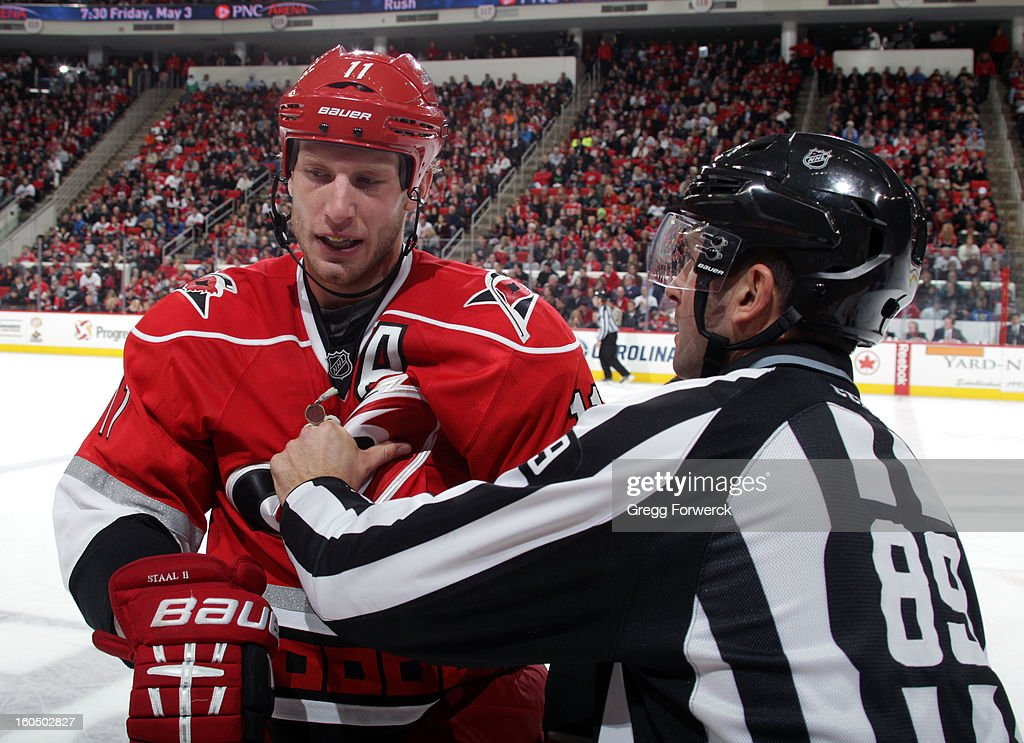 Jordan Staal #11 of the Carolina Hurricanes is directed toward the bench by linesman Steve Miller #89 during an NHL game against the Ottawa Senators at PNC Arena on February 1, 2013 in Raleigh, North Carolina.