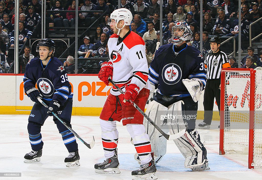<a gi-track='captionPersonalityLinkClicked' href=/galleries/search?phrase=Jordan+Staal&family=editorial&specificpeople=533044 ng-click='$event.stopPropagation()'>Jordan Staal</a> #11 of the Carolina Hurricanes keeps an eye on the play as he positions himself between <a gi-track='captionPersonalityLinkClicked' href=/galleries/search?phrase=Tobias+Enstrom&family=editorial&specificpeople=2538468 ng-click='$event.stopPropagation()'>Tobias Enstrom</a> #39 and goaltender <a gi-track='captionPersonalityLinkClicked' href=/galleries/search?phrase=Al+Montoya&family=editorial&specificpeople=213916 ng-click='$event.stopPropagation()'>Al Montoya</a> #35 of the Winnipeg Jets during second period action at the MTS Centre on March 22, 2014 in Winnipeg, Manitoba, Canada.