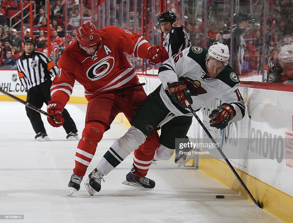 Jordan Staal #11 of the Carolina Hurricanes muscles Dany Heatley #15 of the Minnesota Wild off the puck and into the boards during their NHL game at PNC Arena on November 9, 2013 in Raleigh, North Carolina.