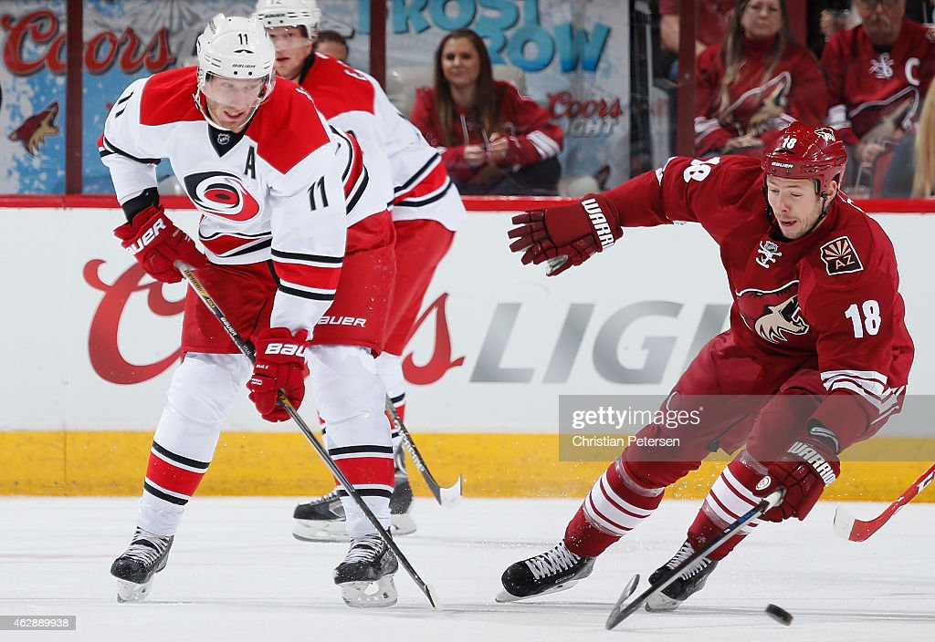 <a gi-track='captionPersonalityLinkClicked' href=/galleries/search?phrase=Jordan+Staal&family=editorial&specificpeople=533044 ng-click='$event.stopPropagation()'>Jordan Staal</a> #11 of the Carolina Hurricanes passs the puck around <a gi-track='captionPersonalityLinkClicked' href=/galleries/search?phrase=David+Moss+-+Jugador+de+hockey+sobre+hielo&family=editorial&specificpeople=6928499 ng-click='$event.stopPropagation()'>David Moss</a> #18 of the Arizona Coyotes during the NHL game at Gila River Arena on February 5, 2015 in Glendale, Arizona.The Hurricanes defeated the Coyotes 2-1 in overtime shootout.