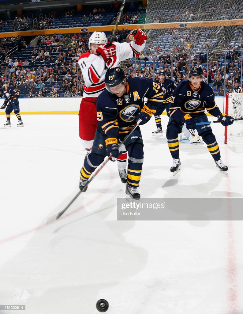 <a gi-track='captionPersonalityLinkClicked' href=/galleries/search?phrase=Jordan+Staal&family=editorial&specificpeople=533044 ng-click='$event.stopPropagation()'>Jordan Staal</a> #11 of the Carolina Hurricanes tries to jump around <a gi-track='captionPersonalityLinkClicked' href=/galleries/search?phrase=Cody+Hodgson&family=editorial&specificpeople=4151192 ng-click='$event.stopPropagation()'>Cody Hodgson</a> #19 of the Buffalo Sabres as they chase the puck at First Niagara Center on September 19, 2013 in Buffalo, United States.