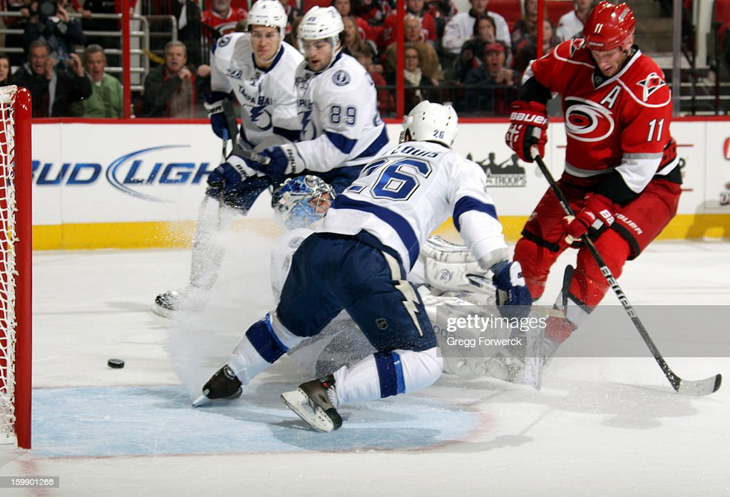 Jordan Staal #11 of the Carolina Hurricanes watches the puck deflect wide of Mathieu Garon #32 of the Tampa Bay Lightning as his teammates swarm to the crease during an NHL game on January 22, 2013 at PNC Arena in Raleigh, North Carolina.
