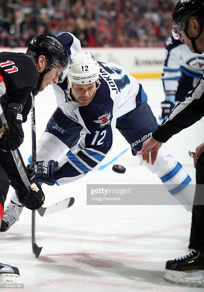 <a gi-track='captionPersonalityLinkClicked' href=/galleries/search?phrase=Jordan+Staal&family=editorial&specificpeople=533044 ng-click='$event.stopPropagation()'>Jordan Staal</a> #11 of the Carolina Hurricanes watches the puck drop during a faceoff against <a gi-track='captionPersonalityLinkClicked' href=/galleries/search?phrase=Olli+Jokinen&family=editorial&specificpeople=202946 ng-click='$event.stopPropagation()'>Olli Jokinen</a> #12 of the Winnipeg Jets during their NHL game at PNC Arena on March 26, 2013 in Raleigh, North Carolina. Both Jordan and brother Eric Staal donned visors for the first time in their NHL careers after brother and New York Rangers defenseman Marc Staal suffered an eye injury after being struck with a puck.