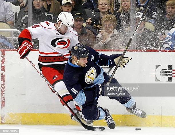 Jordan Staal of the Pittsburgh Penguins and Jaroslav Spacek of the Carolina Hurricanes battle for a puck in the corner during the game at Consol...