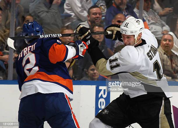 Jordan Staal of the Pittsburgh Penguins gets the stick up on Mark Streit of the New York Islanders at the Nassau Veterans Memorial Coliseum on...