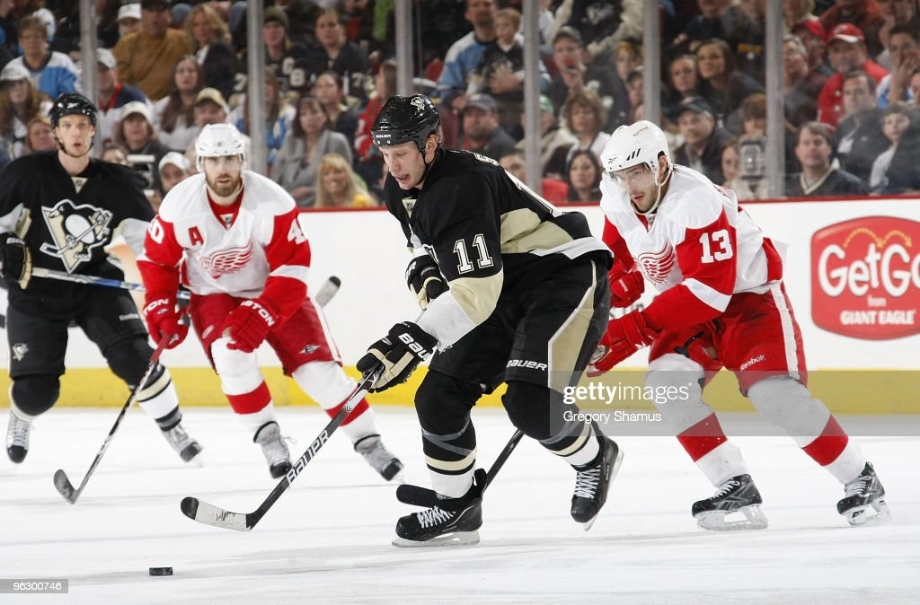 Jordan Staal of the Pittsburgh Penguins moves the puck up ice in front of Henrik Zetterberg and Pavel Datsyuk of the Detroit Red Wings on January 31...