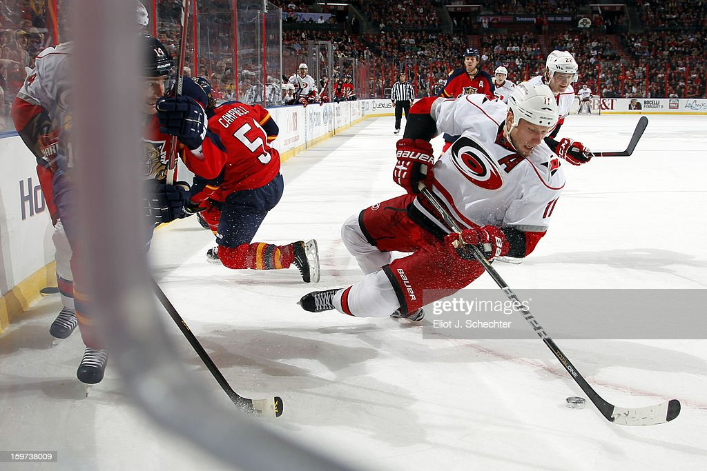Jordan Staal #11of the Carolina Hurricanes digs the puck out from the boards against Tomas Fleischmann #14 of the Florida Panthers at the BB&T Center on January 19, 2013 in Sunrise, Florida.
