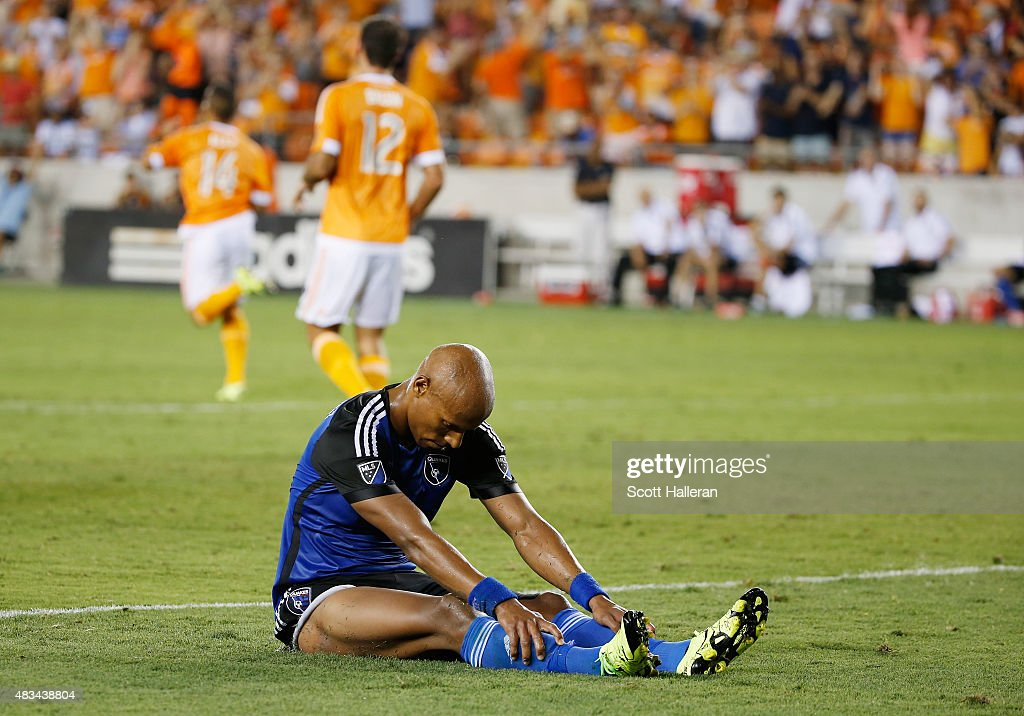 Jordan Stewart #3 of the San Jose Earthquakes sits on the pitch as Alex #14 and Will Bruin #12 of the Houston Dynamo celebrate a second half goal by Alex during their game at BBVA Compass Stadium on August 8, 2015 in Houston, Texas.