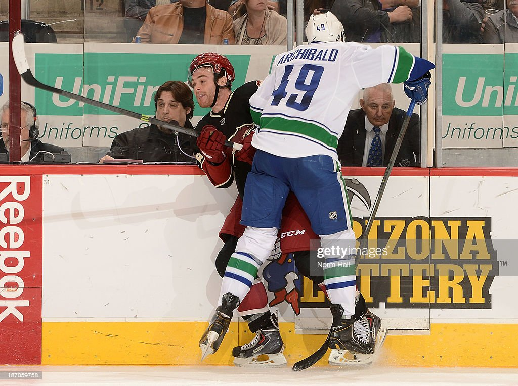 Jordan Szwarz #29 of the Phoenix Coyotes is checked into the boards by Darren Archibald #49 of the Vancouver Canucks during the third period at Jobing.com Arena on November 5, 2013 in Glendale, Arizona.