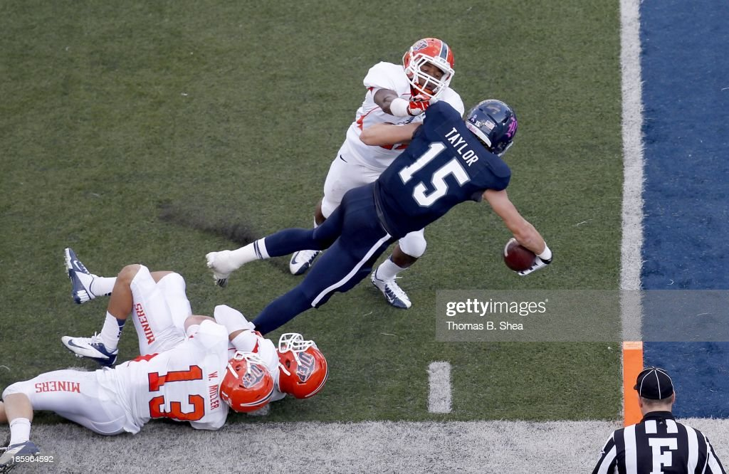 Jordan Taylor #15 of the Rice Owls carries Nick Gathrite #7 of the UTEP Miners after the catch into the end zone for a touchdown on October 26, 2013 at Rice Stadium in Houston, Texas. Rice won 45 to 7.