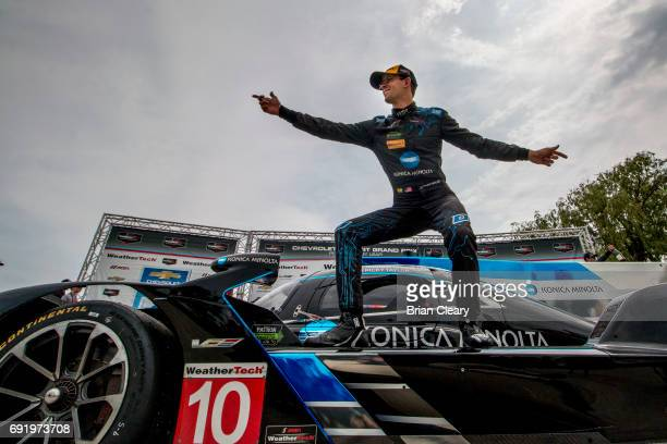 Jordan Taylor strikes a pose atop his race car in victory lane after winning the IMSA WeatherTech Series race at the Detroit Grand Prix at Belle Isle...