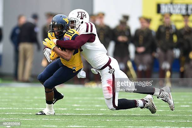 Jordan Thompson of the West Virginia Mountaineers is brought down by Myles Garrett of the Texas AM Aggies during the second quarter of the 56th...