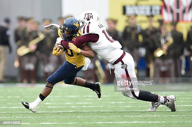 Jordan Thompson of the West Virginia Mountaineers is brought down by Myles Garrett of the Texas AM Aggies during the 56th annual Autozone Liberty...