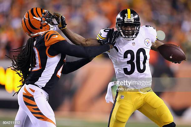 Jordan Todman of the Pittsburgh Steelers stiff arms Reggie Nelson of the Cincinnati Bengals in the first half of the AFC Wild Card Playoff game at...