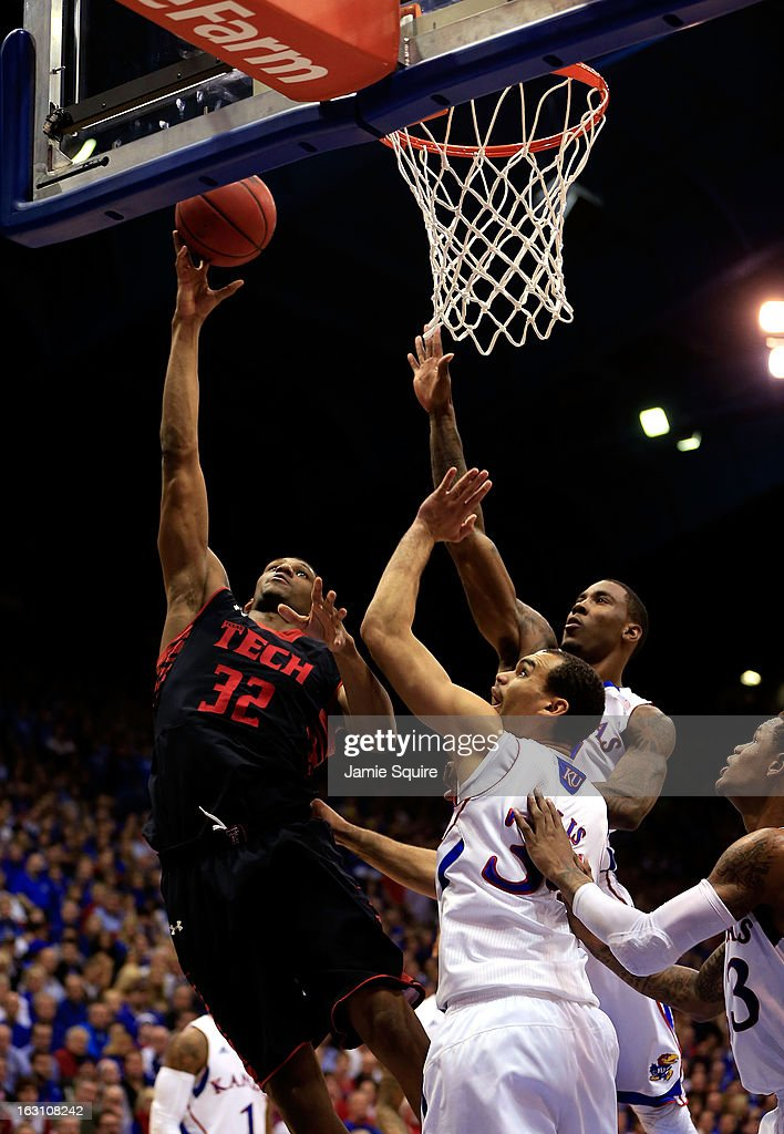 Jordan Tolbert #32 of the Texas Tech Red Raiders shoots over Jamari Traylor #31 and Perry Ellis #34 of the Kansas Jayhawks during the game at Allen Fieldhouse on March 4, 2013 in Lawrence, Kansas.