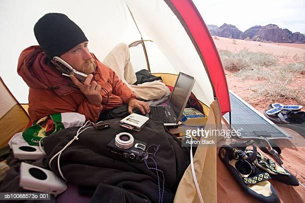 Jordan, Wadi Rum, man using mobile phone in tent