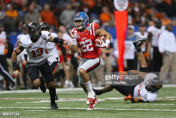 Jordan Wilkins of the Mississippi Rebels carries the ball against Jordan Sterns of the Oklahoma State Cowboys for a touchdown in the third quarter of...