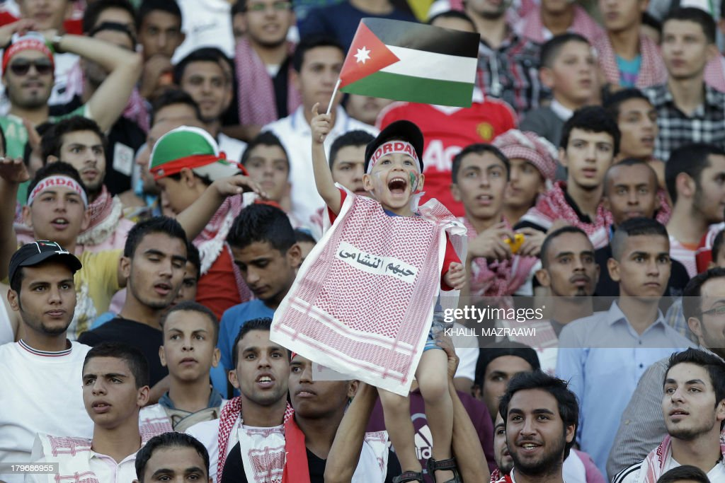 A Jordanese boys waves his national flag and cheers as he watches his national team play their 2014 World Cup qualifier football match against Uzbekistan at the King Abdullah international stadium in Amman on September 6, 2012. The match ended in a draw. AFP PHOTO/KHALIL MAZRAAWI