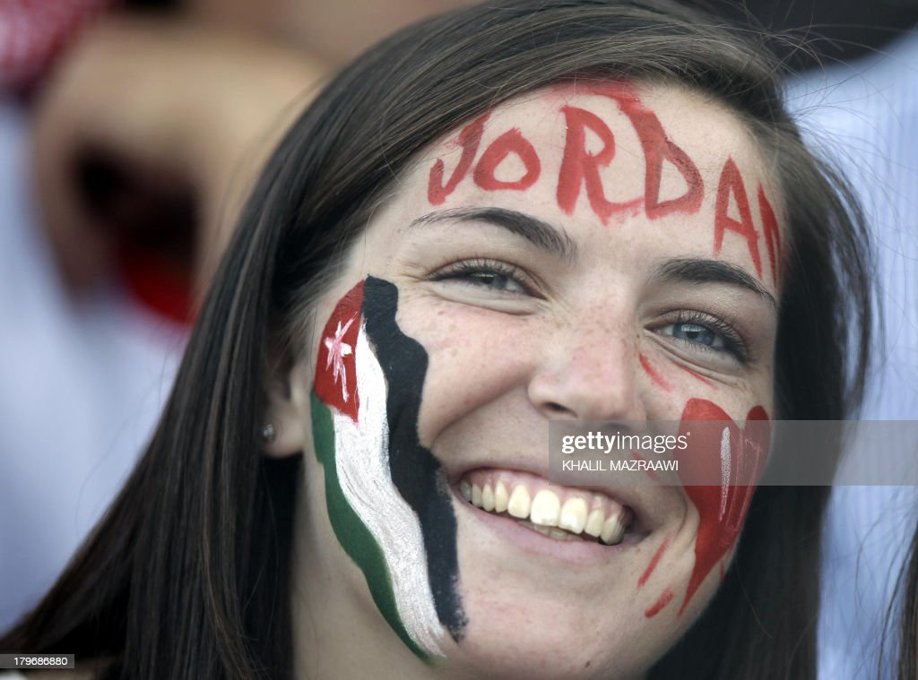 A Jordanese fan smiles as she watches her national team play their 2014 World Cup qualifier football match against Uzbekistan at the King Abdullah international stadium in Amman on September 6, 2012. The match ended in a draw.