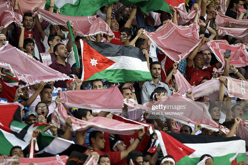 Jordanese fans wave their national flag and traditional Keffiyeh head scarfs as they watch their national team play their 2014 World Cup qualifier football match against Uzbekistan at the King Abdullah international stadium in Amman on September 6, 2012. The match ended in a draw. AFP PHOTO/KHALIL MAZRAAWI