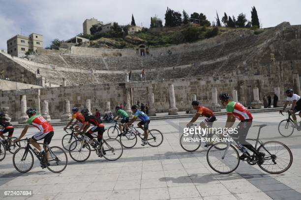 Jordanian and foreign cyclists ride at the ancient Roman theatre in the centre of Amman during a welcome ceremony for members of the Middle East...