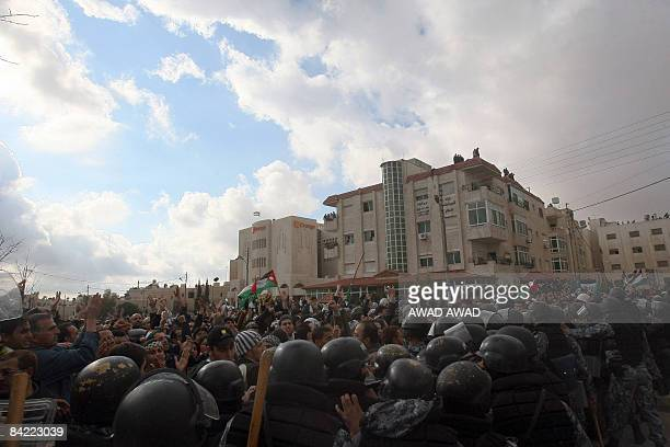 Jordanian and Palestinian protesters clash with Jordanian riot police during a demonstration against the Israeli attacks on the Gaza Strip near the...