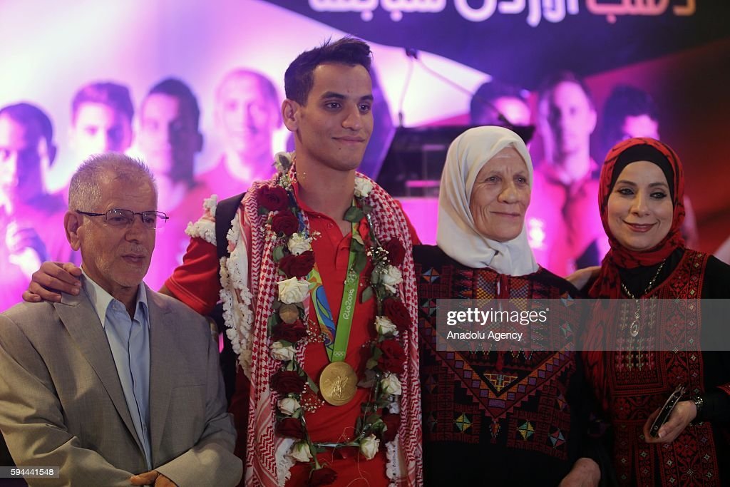 Jordanian athlete Ahmad Abughaush (2nd L), who won gold medal in Men's 68 kg Taekwondo in Rio 2016 Olympic Games, poses with his family after he returned from Rio De Janeiro at Queen Alia International Airport in Amman's Zizya district, Jordan on August 24, 2016.