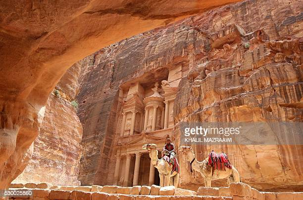 Jordanian Bedouin sits on a camel in front of the Treasury Building in the ancient city of Petra in Jordan on May 9 2016 Established as the capital...