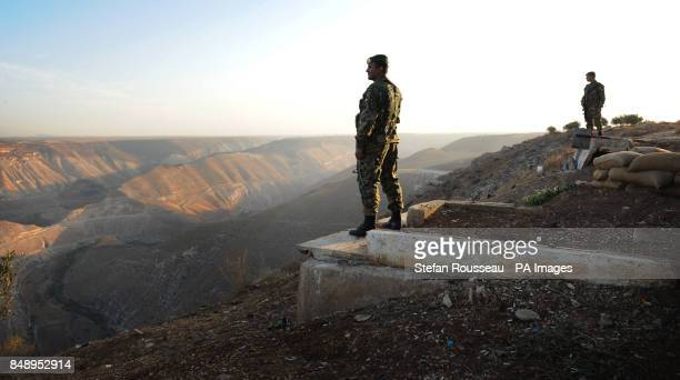 Jordanian border guards look out over Syria from Jordan near the site of the Al Wahdah Dam which is used by many Syrian refugees to escape the Assad...