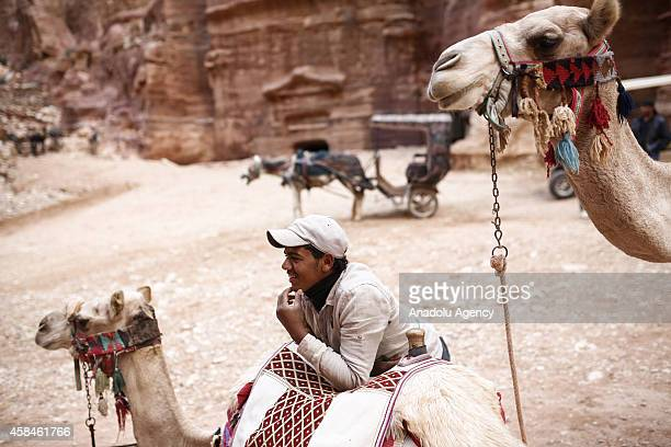 Jordanian boy is seen with camels in front of he facade of Al Khazneh built as a royal tomb and so called after a legend that pirates hid their loot...