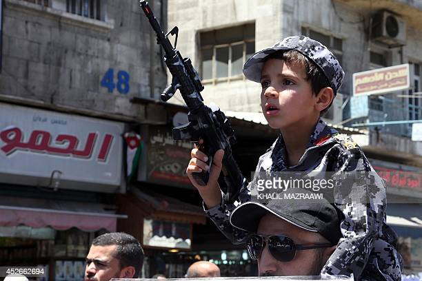 A Jordanian boy on his father's shoulders holds a plastic gun during a protest against the Israeli military offensive in the Gaza Strip and in...