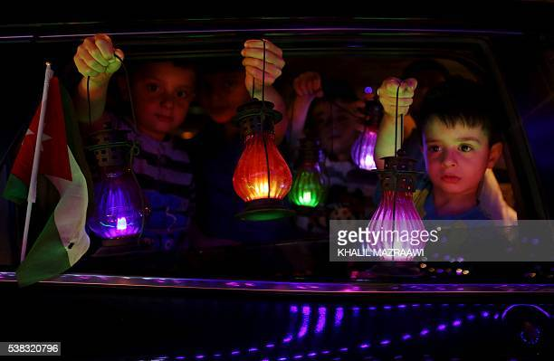 Jordanian children hold traditional lanterns known in Arabic as 'Fanous' sold during the Muslim holy month of Ramadan in the capital Amman on 5 June...
