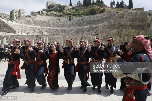 Jordanian dancers wearing traditional clothing perform for Jordanian and foreign cyclists at the ancient Roman theatre in the centre of Amman during...