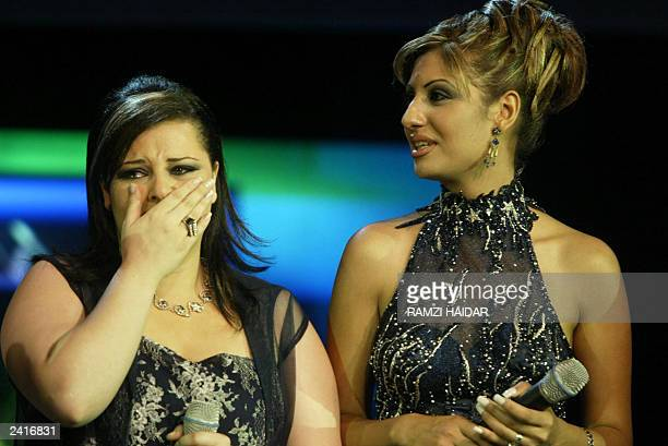 Jordanian Diana Karzon cries after winning the title of Arabs Superstar as Syrian Ruweida Attiyeh stands next to her late 18 August 2003 in Beirut...