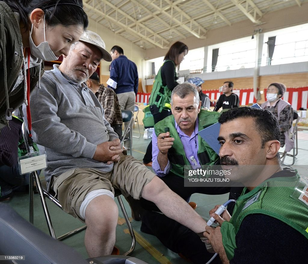 Jordanian doctor Omar Nayel Zubi and nurse Abdallah Alzumbi check an elderly man for deep vein thrombosis at a shelter in the city of Minamisoma in...