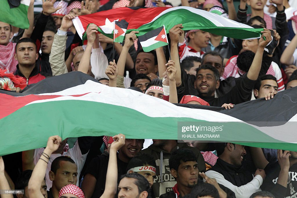 Jordanian fans wave their national flag as their cheer on their team prior to the start of their FIFA World Cup Group B Asian qualifiers round four football match against Japan, in Amman, on March 26, 2013. AFP PHOTO/KHALIL MAZRAAWI