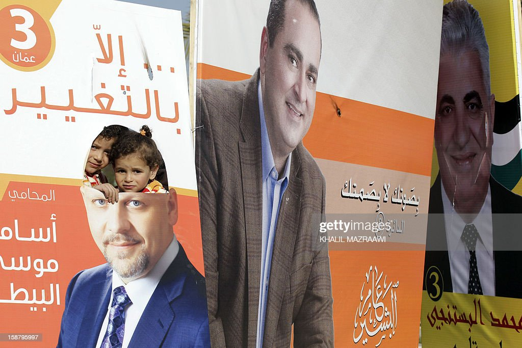 Jordanian kids look through a hole in one of the pictures of parliament candidates in Amman on December 29, 2012. Jordan's electoral authority set January 23 as the date for a general election after King Abdullah II dissolved parliament despite a boycott pledge by the opposition Muslim Brotherhood.