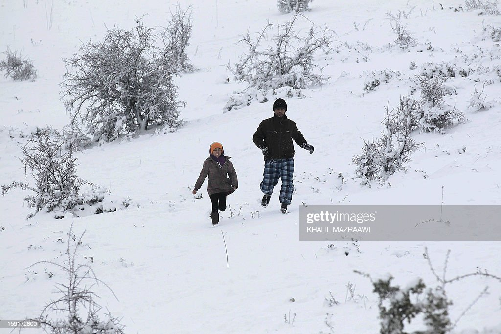 A Jordanian man and a child play on the snow in Amman, on January 9, 2013. Extreme weather, including torrential rains and heavy winds, killed four people in Israel and the Palestinian territories on January 8, as widespread flooding swept the Middle East.