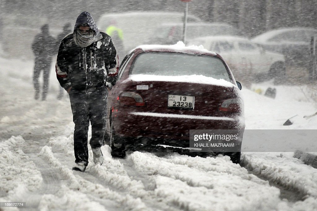 A Jordanian man walks past a vehicle as snow falls over Amman, on January 9, 2013. Extreme weather, including torrential rains and heavy winds, killed four people in Israel and the Palestinian territories on January 8, as widespread flooding swept the Middle East.