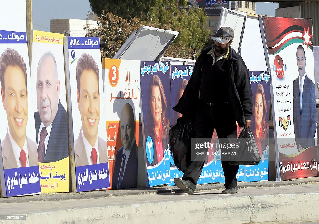 Jordanian man walks past electoral campaign posters in Amman on January 19, 2013. Jordanians go to the polls on January 23, but an Islamist boycott is expected to produce a toothless parliament that is unlikely to bring real reform, leaving the country in political uncertainty.