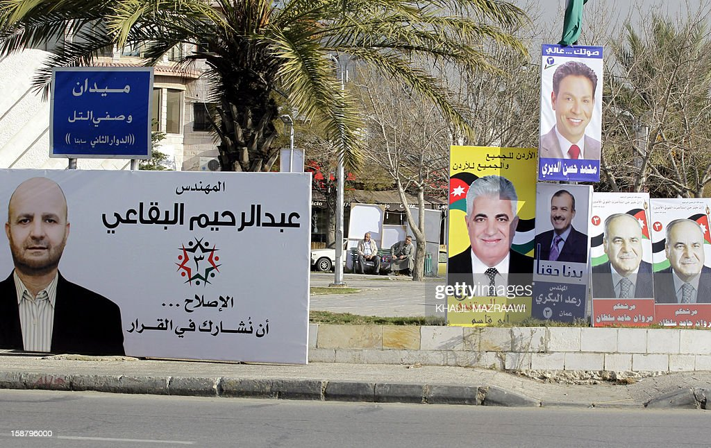 Jordanian men sit near pictures of parliament candidates in Amman on December 29, 2012. Jordan's electoral authority set January 23 as the date for a general election after King Abdullah II dissolved parliament despite a boycott pledge by the opposition Muslim Brotherhood.