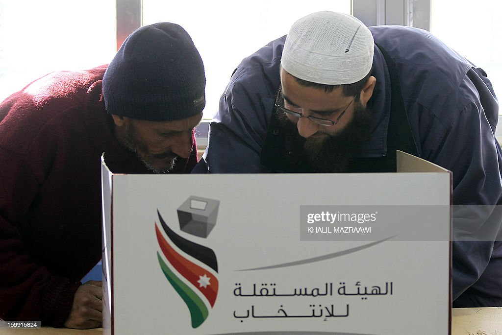Jordanian men stand behind a voting booth at a polling station in the Palestinian refugee camp of Baqaa, north of Amman, on January 23, 2013. Jordanians are voting in a parliamentary poll snubbed by Islamists who have staged strident pro-reform protests and who have already slammed what is expected to be an opposition-free body as illegitimate. AFP PHOTO/KHALIL MAZRAAWI