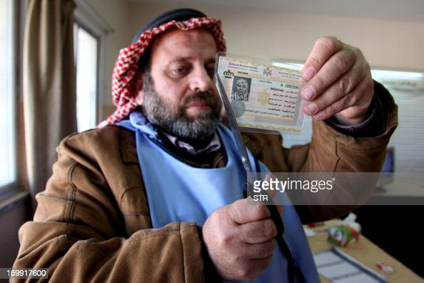 A Jordanian observer cuts the voter ID card of a woman after she cast her ballot at a polling station in Amman on January 23 2013 Jordanians are...