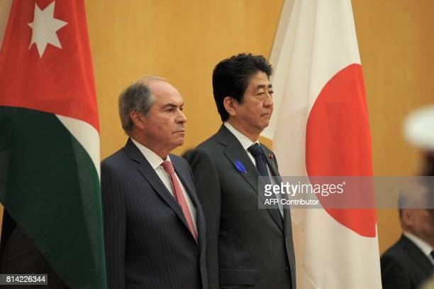 Jordanian Prime Minister Hani alMulki Japanese Prime Minister Shinzo Abe listen to the national anthems during a welcoming ceremony at the Prime...