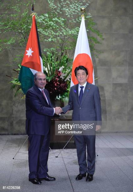 Jordanian Prime Minister Hani alMulki shakes hands with Prime Minister Shinzo Abe before their meeting at the Prime Minister Office in Tokyo on July...