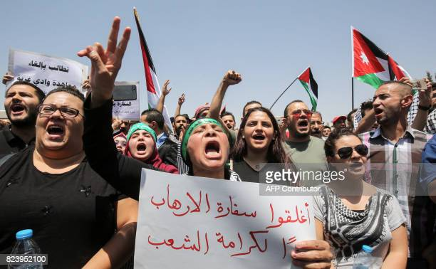 A Jordanian protester flashes the victory gesture as she holds a sign calling for closing down the Israeli embassy in the capital Amman on July 28...