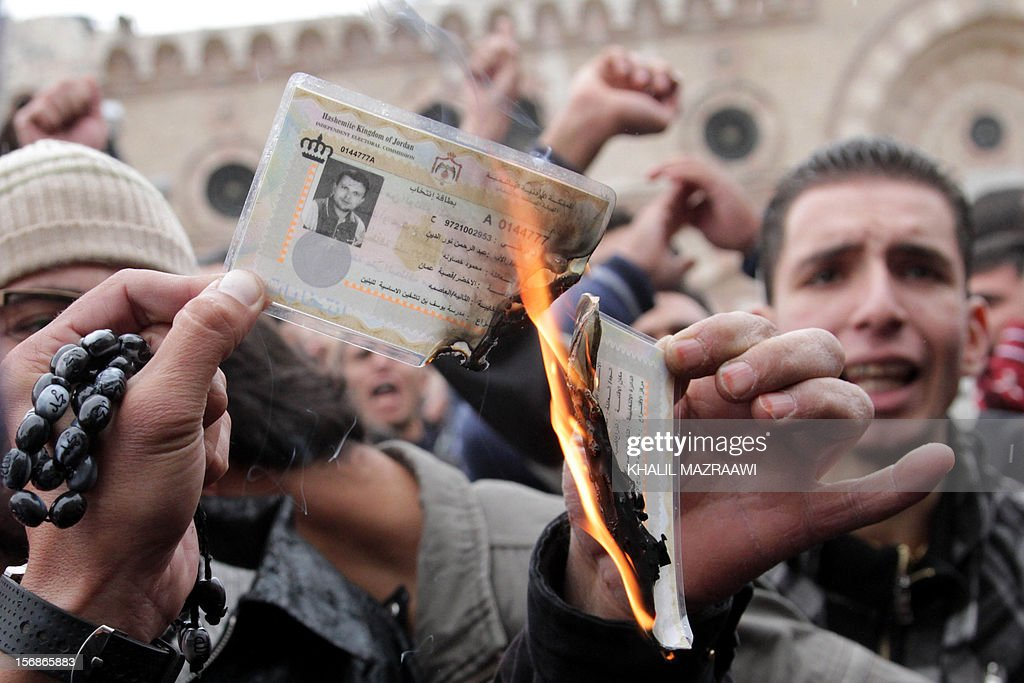 Jordanian protesters burn identity cards to encourage citizens to boycott the country's upcoming parliamentary elections in front of the Al-Hussein mosque in Amman on November 23, 2012, during a rally against rising fuel prices and calling for political and economic reform. Around 300 people, including Islamists and leftists, demonstrated chanting slogans that included calls for the government to step down.