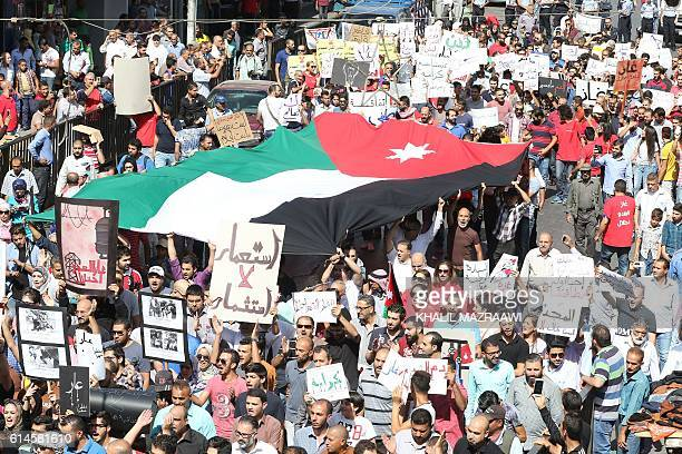 Jordanian protesters deploy a giant national flag and hold placards during an Islamistled opposition protest against a deal with Israel to import...