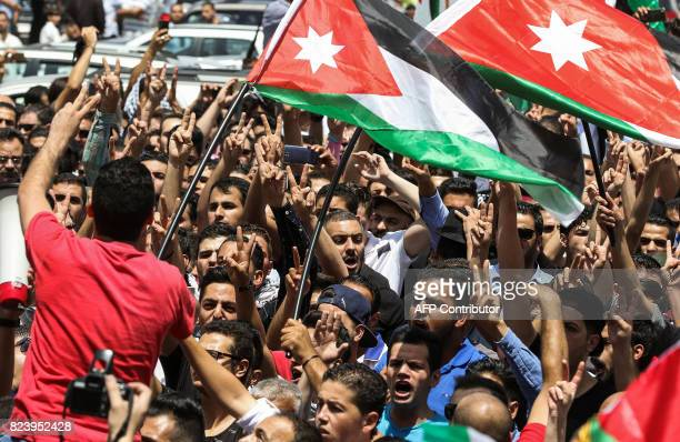 Jordanian protesters flash the victory gesture as they wave national flags and chant slogans during a demonstration near the Israeli embassy in the...
